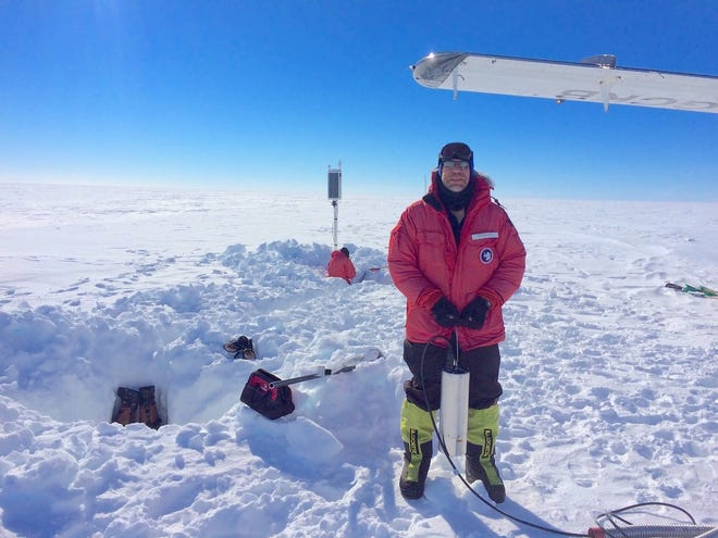 Rick Aster, a Colorado State University scientist, stands on Antarctica's Ross Ice Shelf, holding a seismometer that detected eerie sounds in the ice.