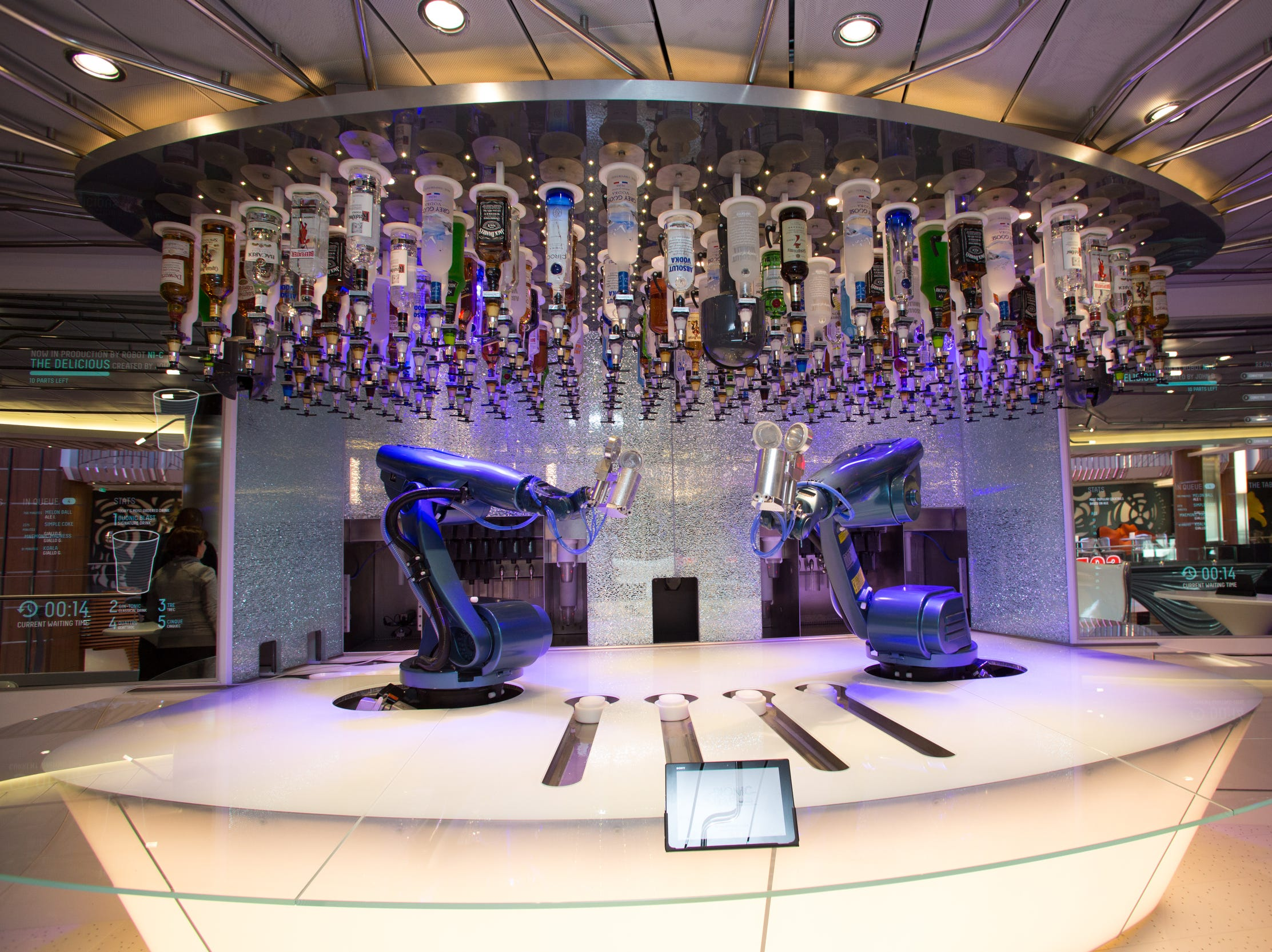 Passengers use an iPad to place orders for drinks at the Bionic Bar on Royal Caribbean's Quantum of the Seas. The robot bartenders do the rest.