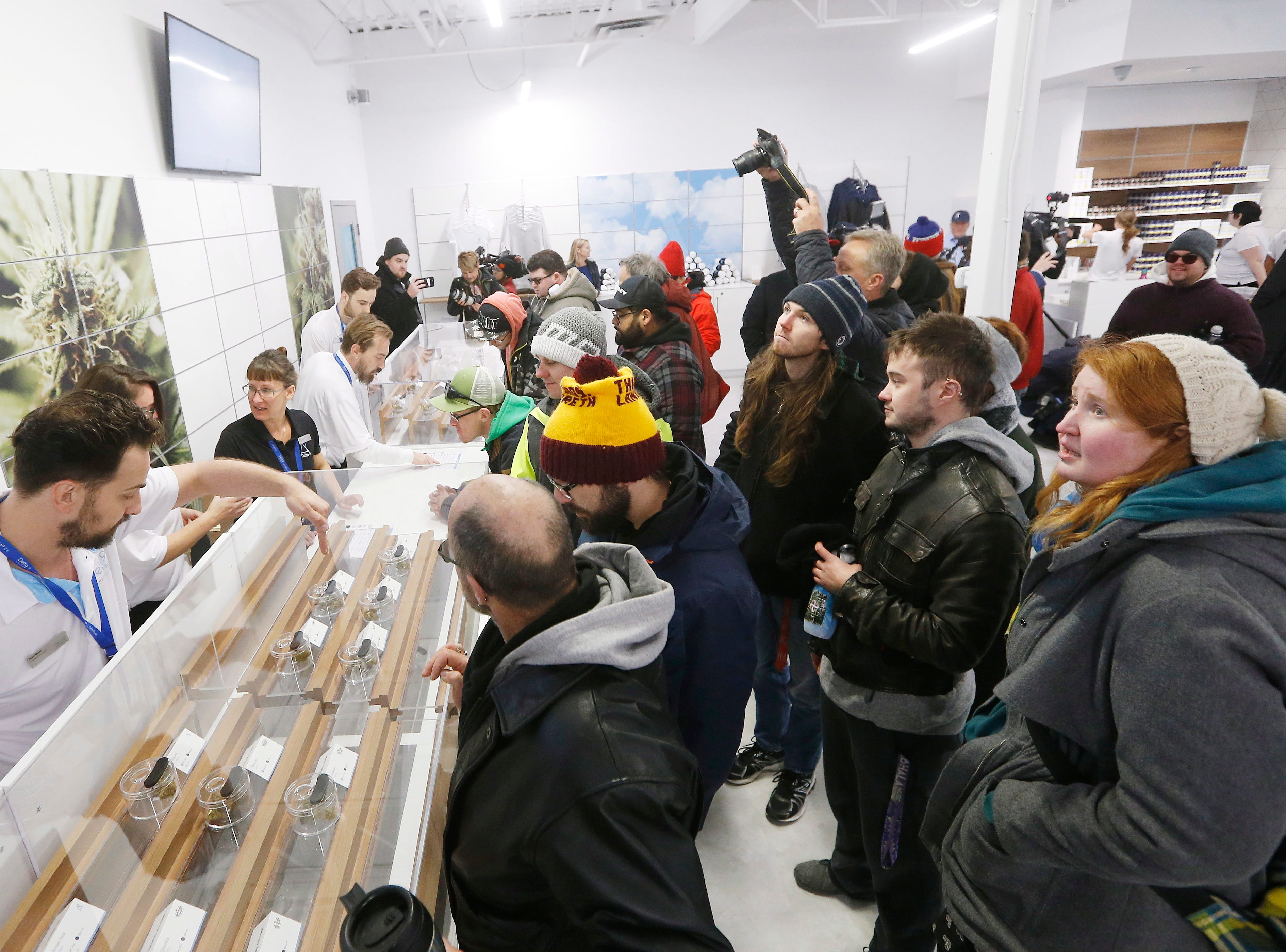 People check out the sample counter at a cannabis store in Winnipeg, Manitoba, on Wednesday, Oct. 17, 2018. Canada became the largest country with a legal national marijuana marketplace as sales began early Wednesday.