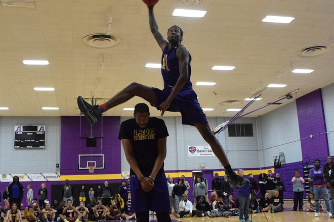 LSUA men's basketball player Phillip Rankin (top) jumps over teammate Rickey Brice Jr. while performing a slam dunk Wednesday during the LSUA Midday Madness.