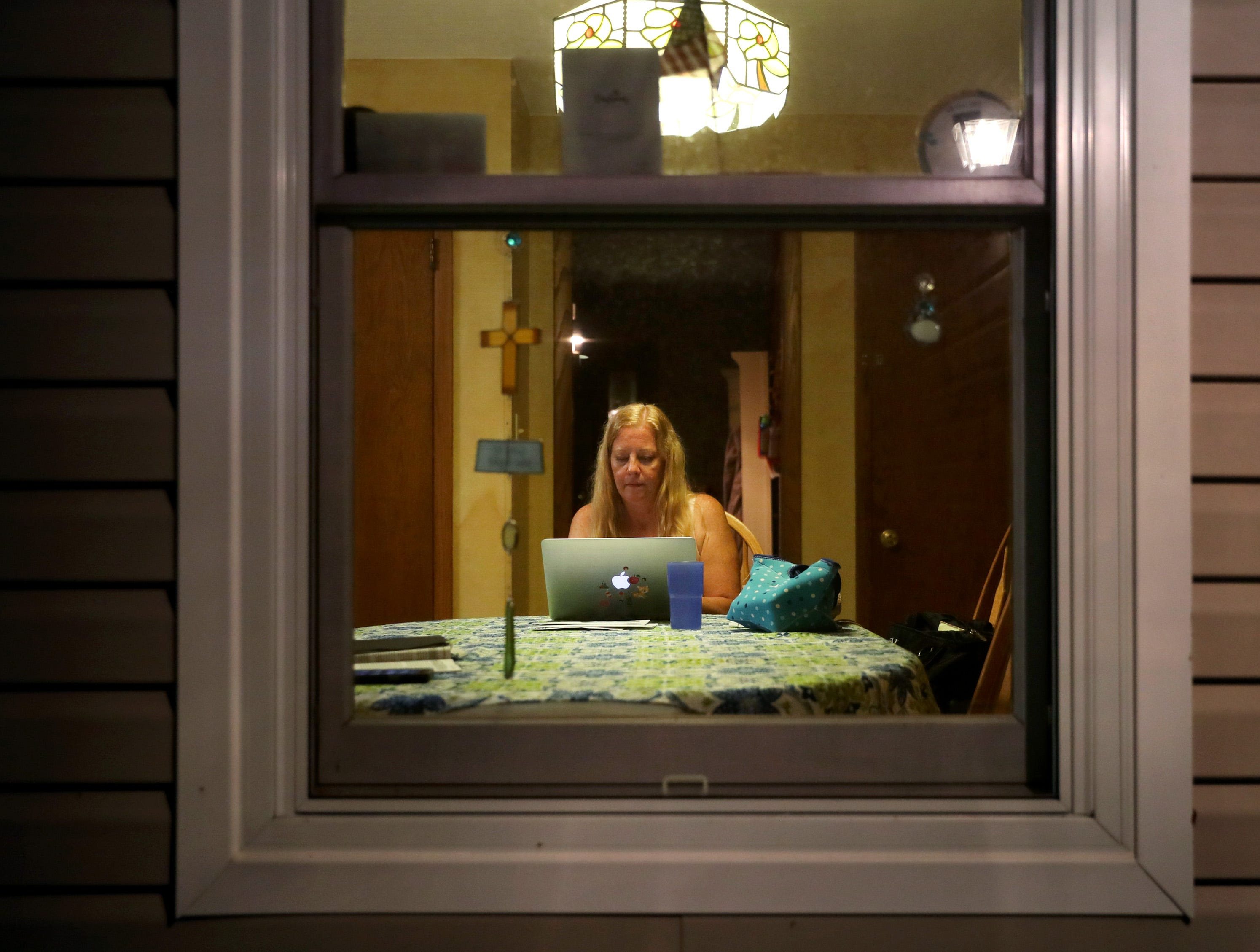Maripat Franke, a special education teacher at Neenah High School currently enrolled in the Residency In Teacher Education 2.0 program at CESA 6, can be seen through her kitchen window checking emails after finishing her workday and teaching a baton twirling class at the Neenah/Menasha YMCA Monday, Sept. 17, 2018, in Neenah, Wis.