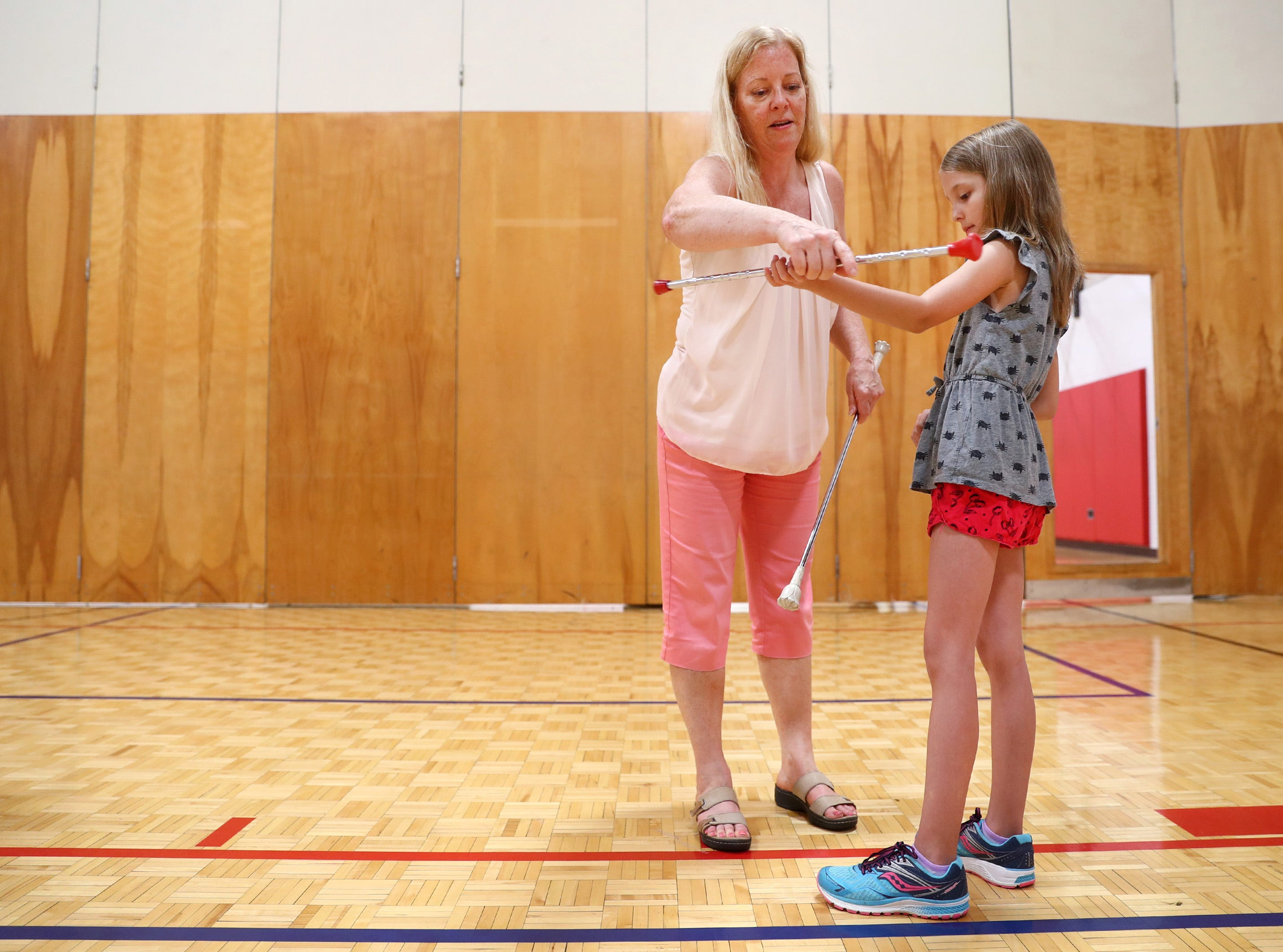 Maripat Franke, a special education teacher at Neenah High School currently enrolled in the Residency In Teacher Education 2.0 program at CESA 6, works with Cecelia Preman, 8, while teaching a baton twirling class at the Neenah/Menasha YMCA Monday, Sept. 17, 2018, in Neenah, Wis. Franke teaches the class Monday nights after school.