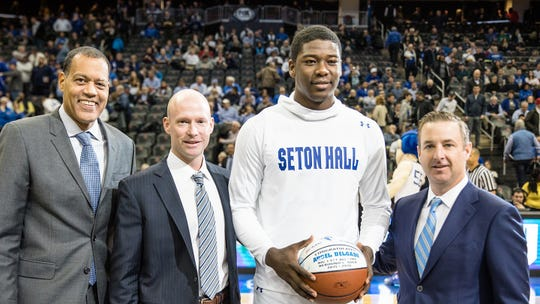 Seton Hall AD Pat Lyons (far right), with Hall coach Kevin Willard and Stu Jackson of the Big East, present Angel Delgado with a ball commemorating the league's career rebounding record in 2018