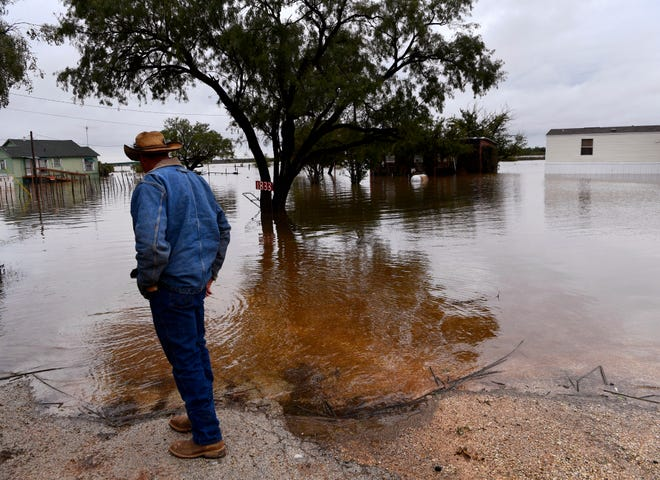 Chris Haas surveys the floodwaters surrounding his cabin at Lake Stamford Thursday Oct. 18, 2018. Heavy rains have filled the lake to overflowing, flooding homes along the shore for the first time in several years.