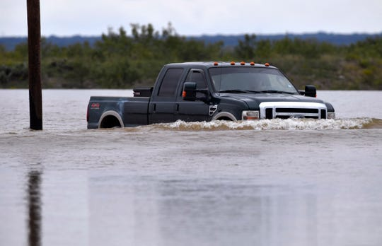 A motorist drives across the Lake Fort Phantom Hill spillway Thursday Oct. 18, 2018. Floodwaters were covering the flood gauge at the two-foot mark and were still rising.