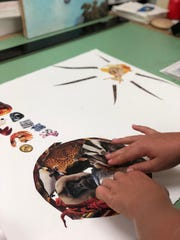 A middle-schooler works on self-portraits using collage.