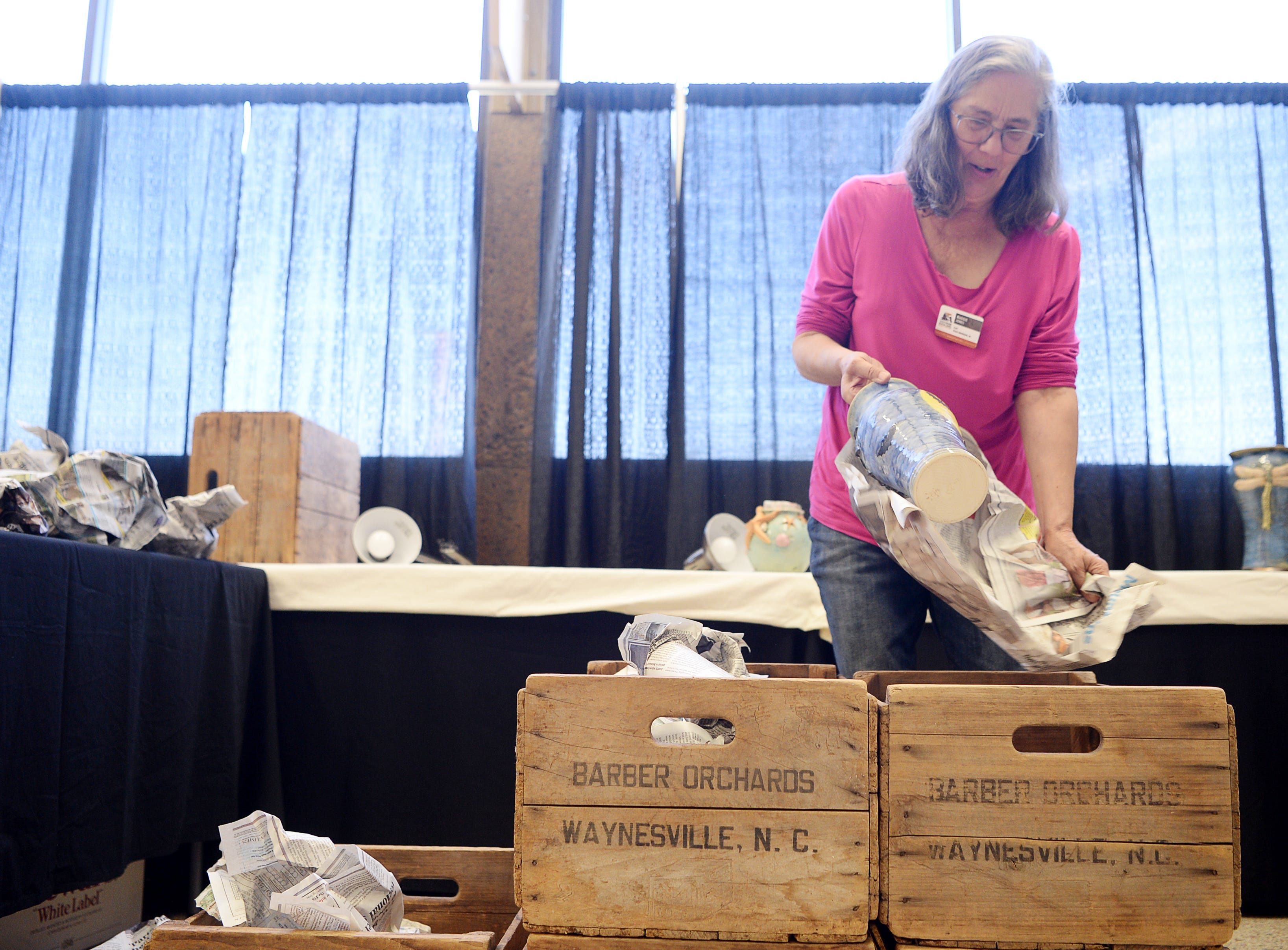 Maggie Jones prepares the Turtle Island Pottery booth as she gets ready for this weekend's Craft Fair of the Southern Highlands.