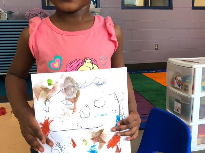 A student at the YWCA of Asheville holds her self-portrait.