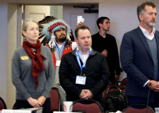 Jesse Nightwalker of Tacoma, Wash., a member of the Palouse tribe, wears a ceremonial headdress as he takes video during a meeting of the Southern Resident Killer Whale Recovery Task Force in Tacoma. Nightwalker said he is in support of calls to breach four hydroelectric dams in Washington state as the plight of the critically endangered Northwest orca whales has captured global attention.