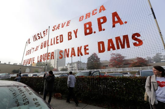 Supporters of measures intended to help endangered orca whales stand near a large sign a outside a building in Tacoma, where the Southern Resident Killer Whale Recovery Task Force was meeting for a two-day work session.