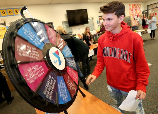"""Freshman Jeremy Ford gives the """"Reality Wheel"""" a spin during It's Your Future Fair at Bremerton High School."""