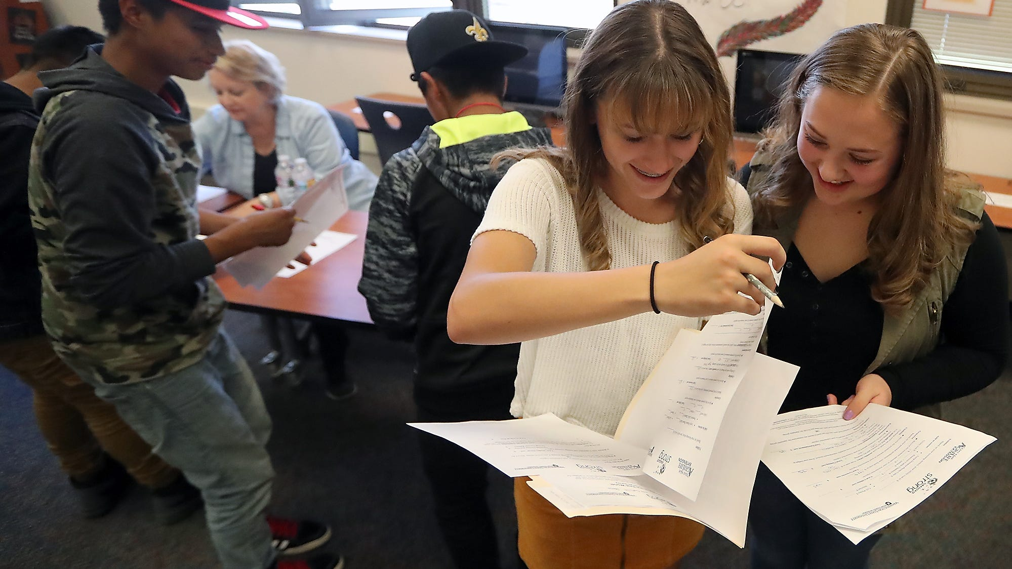 Freshmen classmates Cecilia Souza (left) and Marli Stodden look over their budget sheets as they take part in It's Your Future Day at Bremerton High School on Thursday, October 18, 2018.