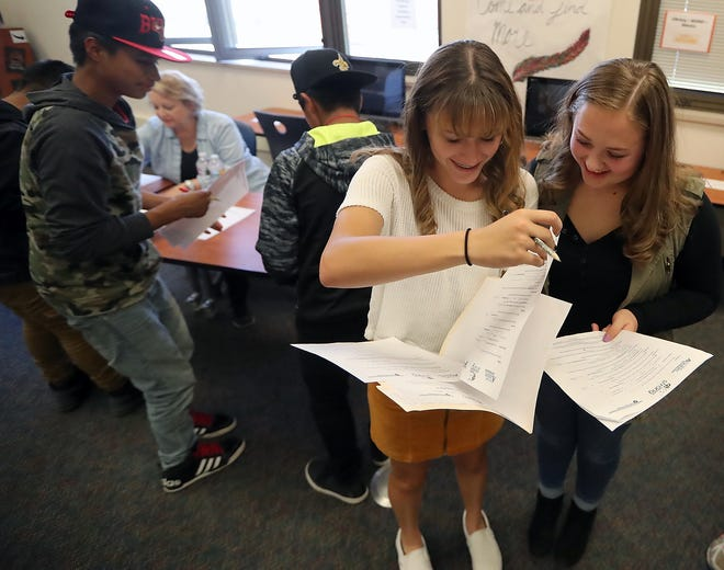 Freshmen classmates Cecilia Souza, left, and Marli Stodden look over their budget sheets as they take part in It's Your Future Fair at Bremerton High School on Thursday.