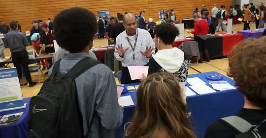 Boeing's lead recruiter Jon McClain, center, talks with students about careers at Boeing while taking part in It's Your Future Fair at Bremerton High School on Thursday.