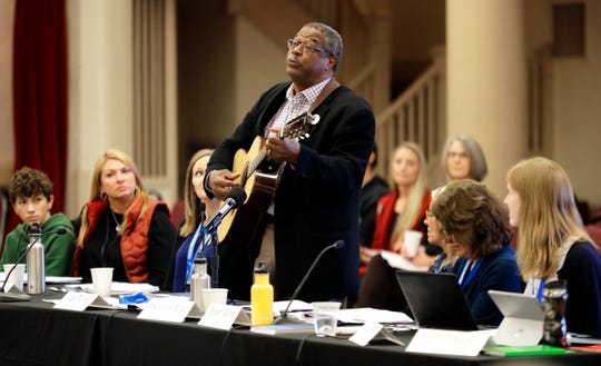 Les Purce, co-chair of the Southern Resident Killer Whale Recovery Task Force, plays guitar and sings during the opening of a two-day meeting of the task force in Tacoma. Calls to breach four hydroelectric dams in Washington state have grown louder in recent months as the plight of the critically endangered Northwest orcas has captured global attention.