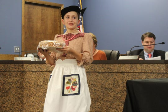 """Dressed as Claudia Crawford McGraw, Pearl Hall presents pound cake made from the recipe used by the """"Apron Lady"""" to the board of aldermen on Oct. 8."""