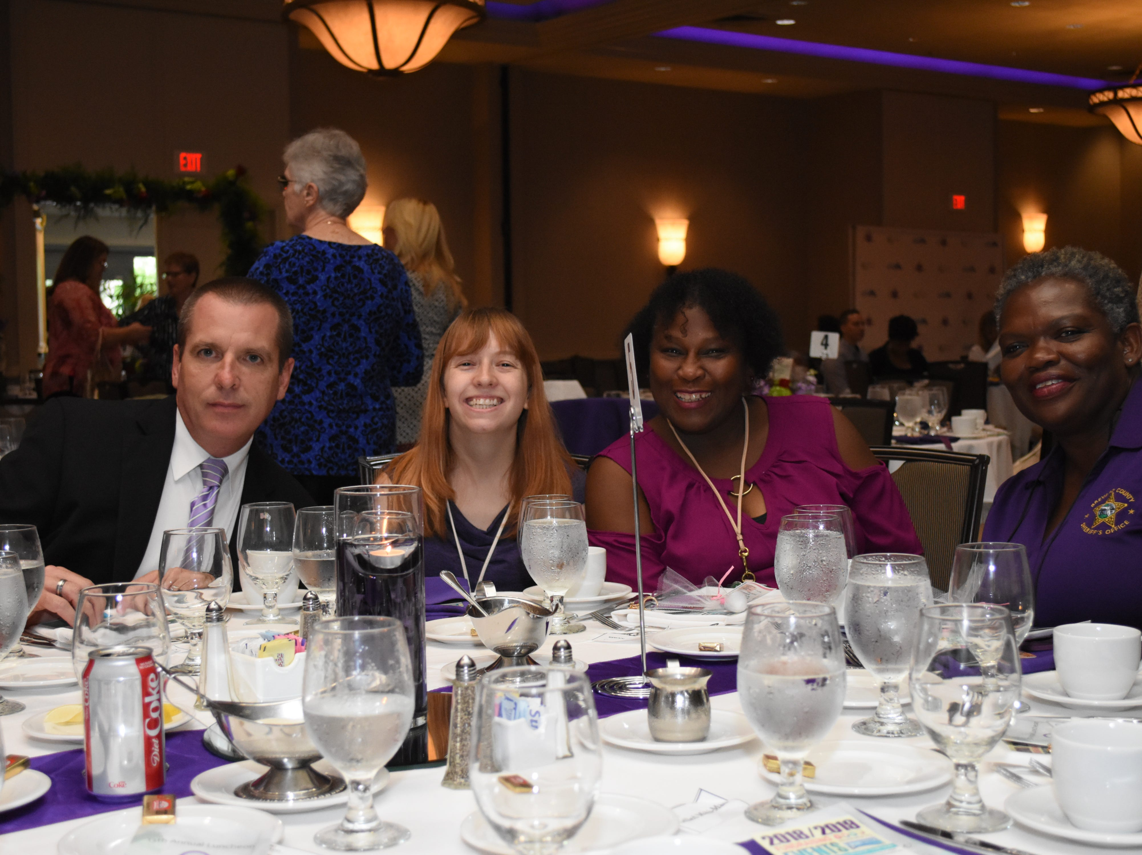 Alan Morrison, Ashley Wong, Cynthia Matthews, and Peggy Brooks with the Brevard Sherrifs office pose for a photo at their table.