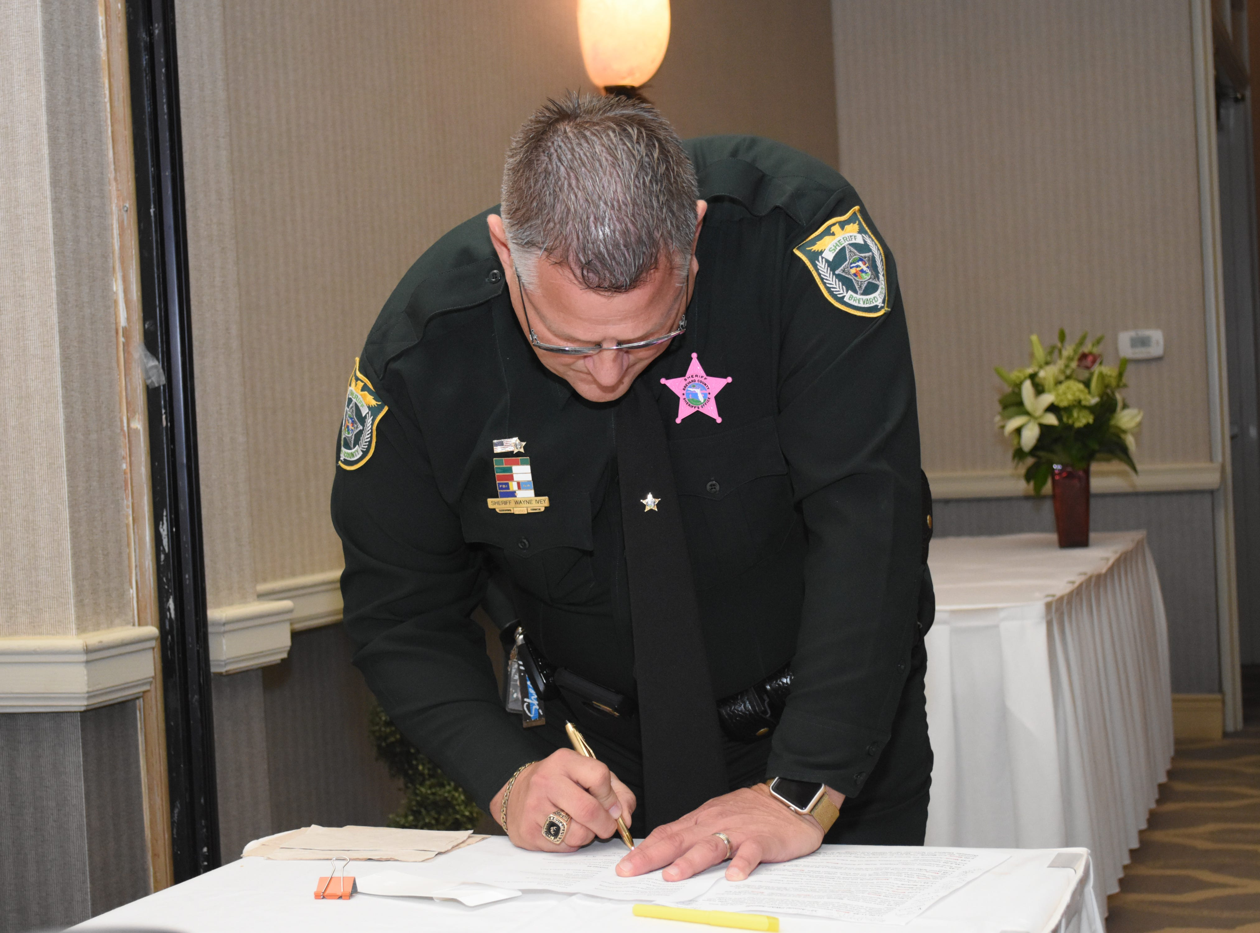 Sheriff Wayne Ivey looks over details of the live auction items that he will auction off.
