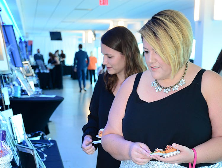 Cheyenne McCully and Jessica Kane look over some of the items up for silent auction Saturday night at Port Canaveral during the Fly Me to The Moon gala.