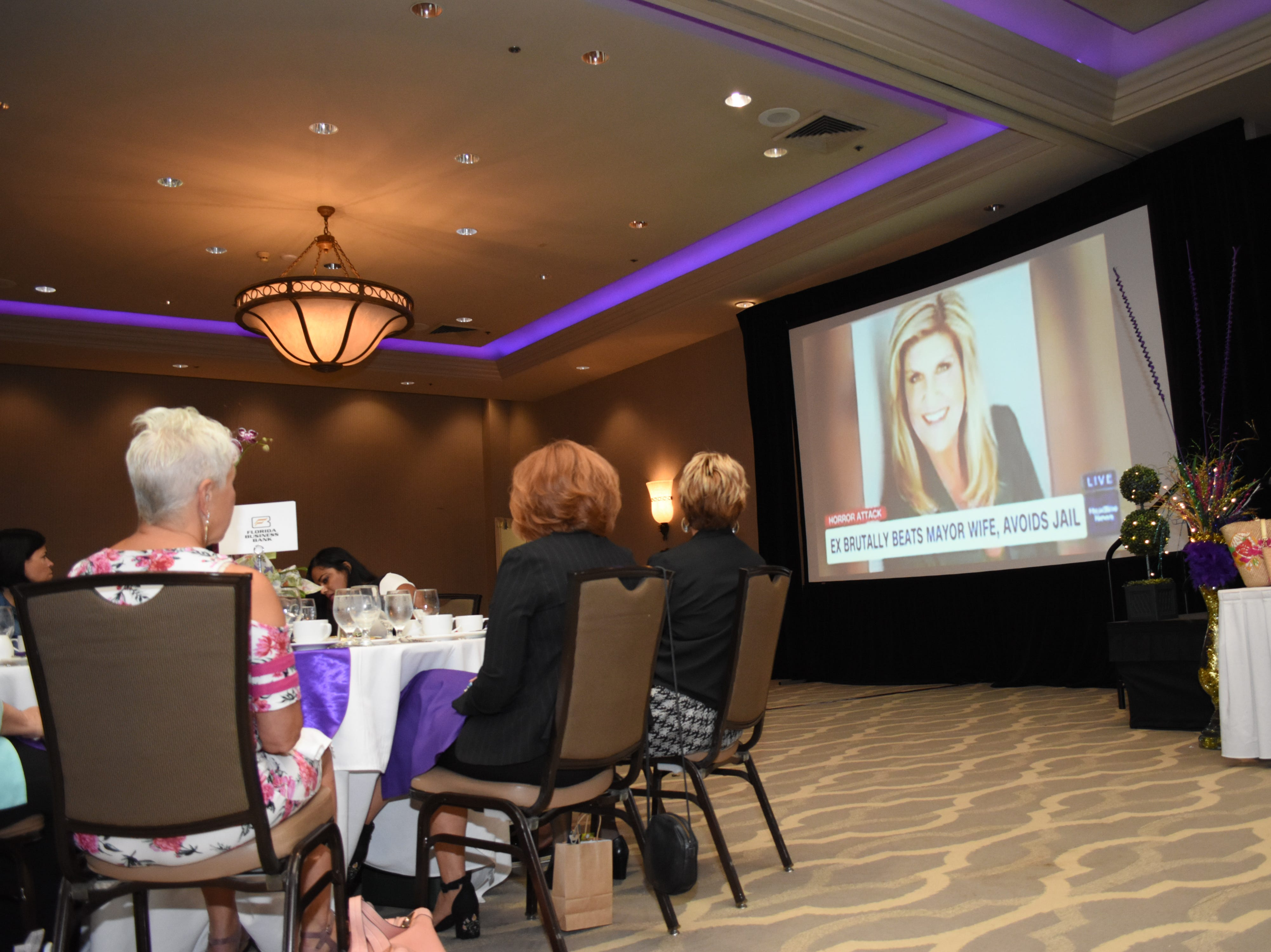 Guests watch a video about Former mayor of Cape Coral Marni Sawicki's experience with domestic abuse.