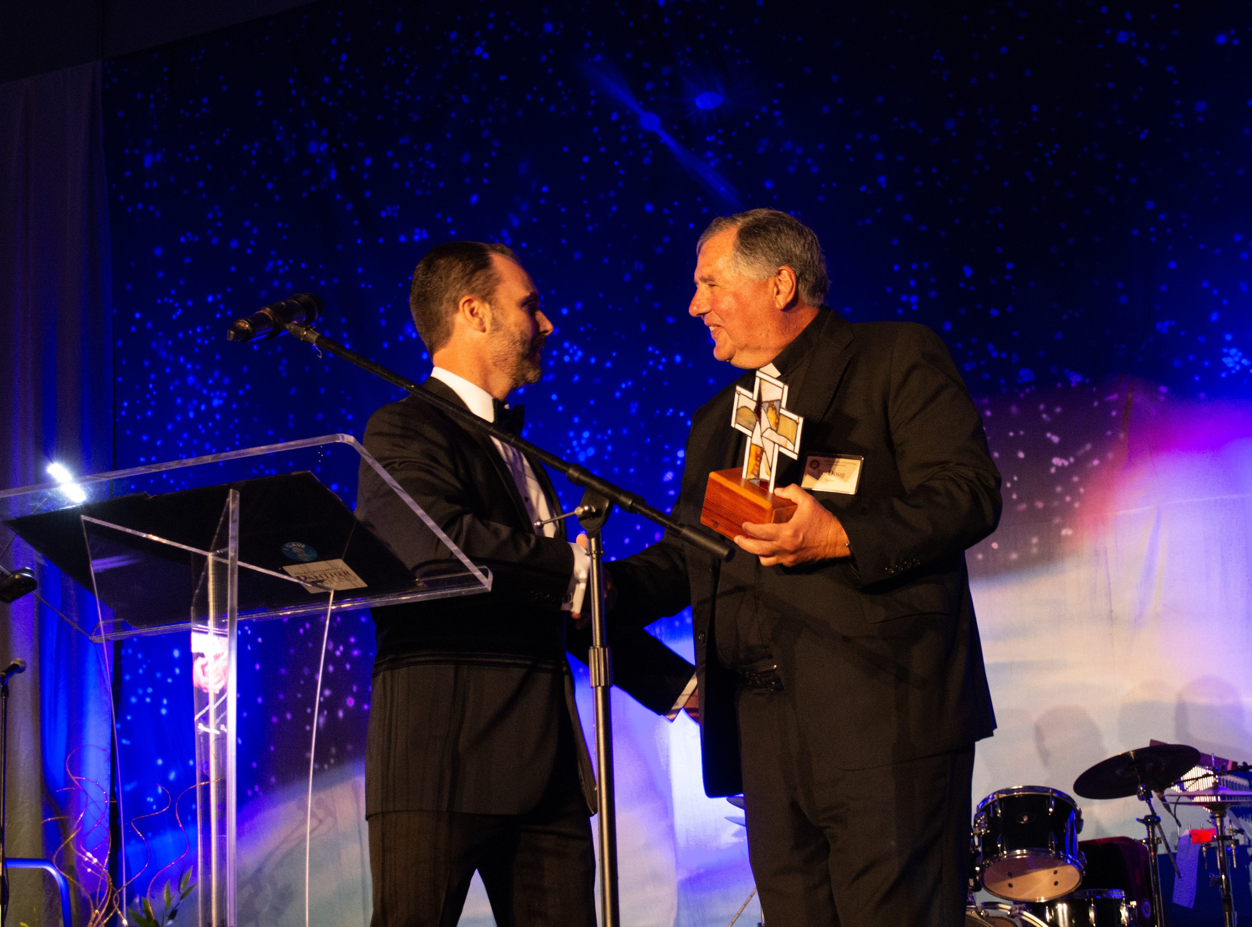 Fr. Doug Bailey, SDS, receives an award from Florida Tech's Execuitive Director of the Alumni Association and Master of Ceremonies Bino Campanini at Florida Tech's 60th Anniversary Homecoming Gala Oct. 13, 2018, at the Clemente Center.