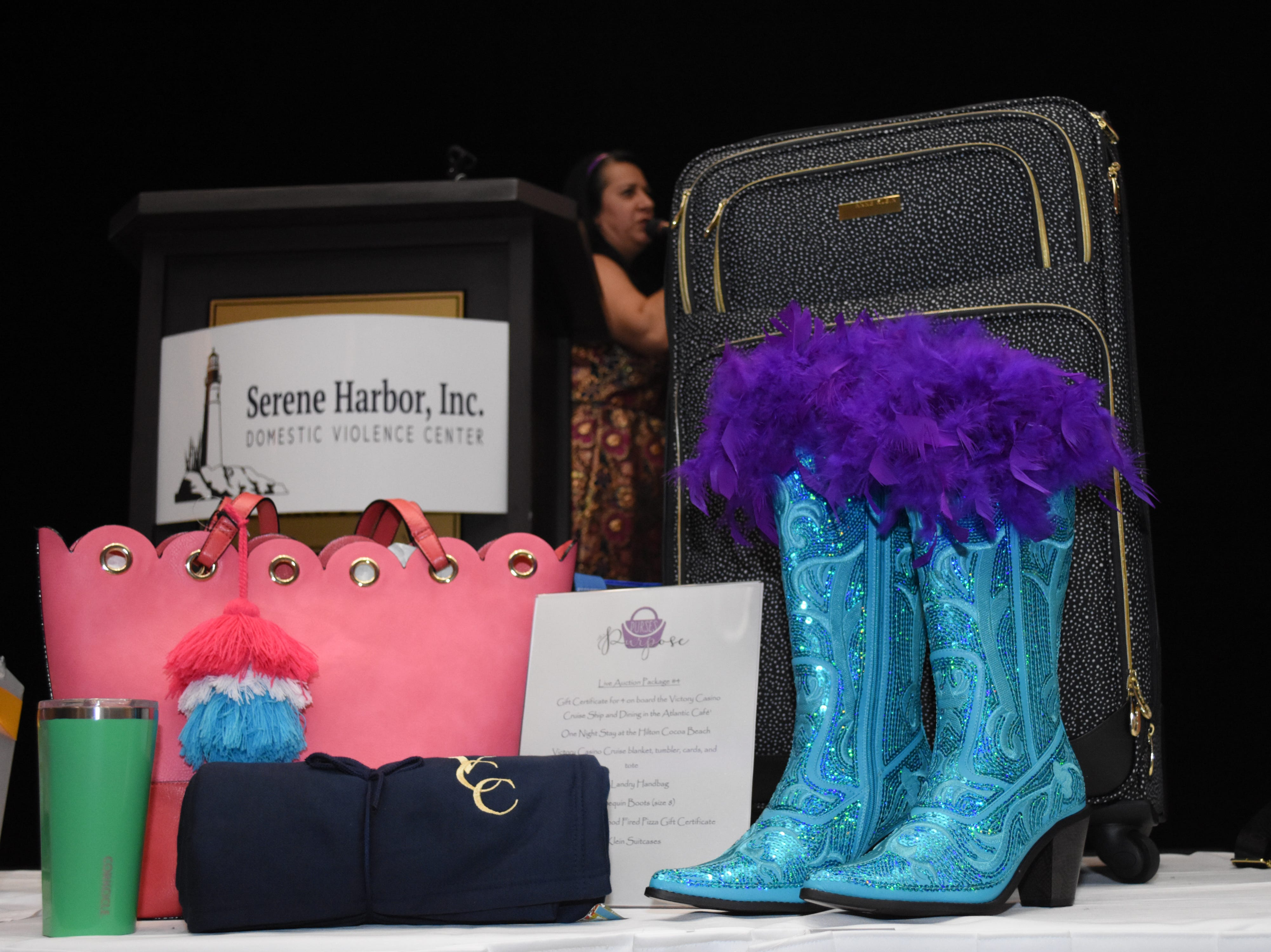 Live auction photos displayed infront of the stage at the 2018 Purses with a Purpose fundraiser.