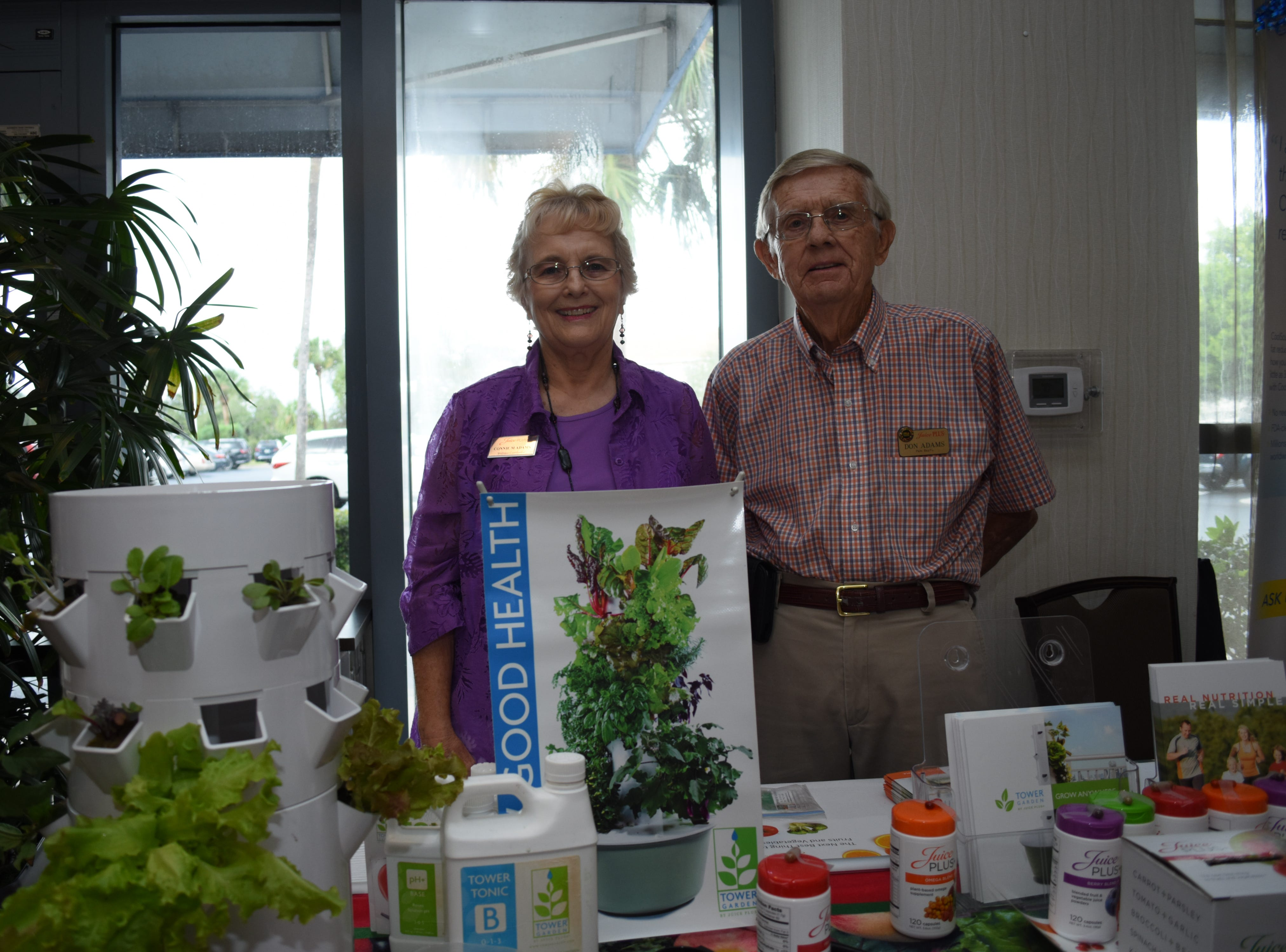 Connie and Don Adams with Juice PLUS pose for a photo with their table.