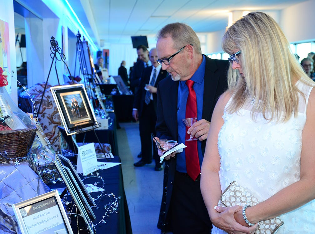 Tracy Mileage and Greg Hahn scan over some of the items up for silent auction Saturday evening at Port Canaveral.