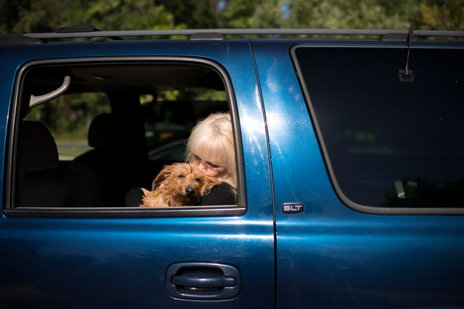 Kathy Tortu-Bowles holds Pudge while putting his leash on inside her car Wednesday, Oct. 17, 2018 in Voorhees, N.J. Kathy helped search for Pudge, who went missing in June. She ultimately rescued him after installing cameras and a trap behind an apartment complex in Voorhees.