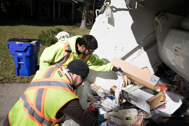 Ryan Owen, left, and Erik Bouillon quickly inspect some of the recently dumped recycled material obtained at Brewer Heights Thursday afternoon in Chillicothe.