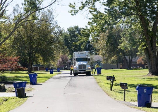 Recycling collection employees for Chillicothe empty recycling containers lined down Shawnee Drive Thursday afternoon in the Brewer Heights subdivision.