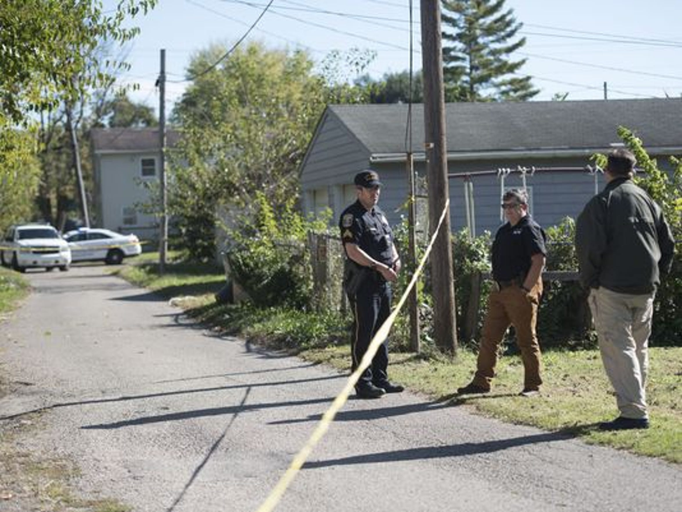 Police wait for the coroner shortly after the body of a male was found the morning of Oct. 18 in the backyard of a 300 block of East Second Street home.