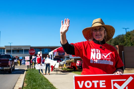 Donna Kent waves to passing cars during early voting at the Montgomery County Election Commission Thursday, Oct. 18, 2018, in Clarksville, Tenn.