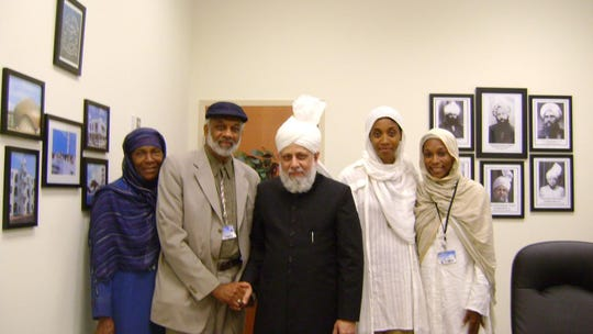 Withthree stops on the East Coast beginning Friday, Oct. 19, thousands are expected to make the pilgrimage to see international Muslim leader, His Holiness Mirza Masroor Ahmad, duringhis U.S. visit. Here, Aliya Latif (all in white) and her family meet with the Khalifa during a recent visit.