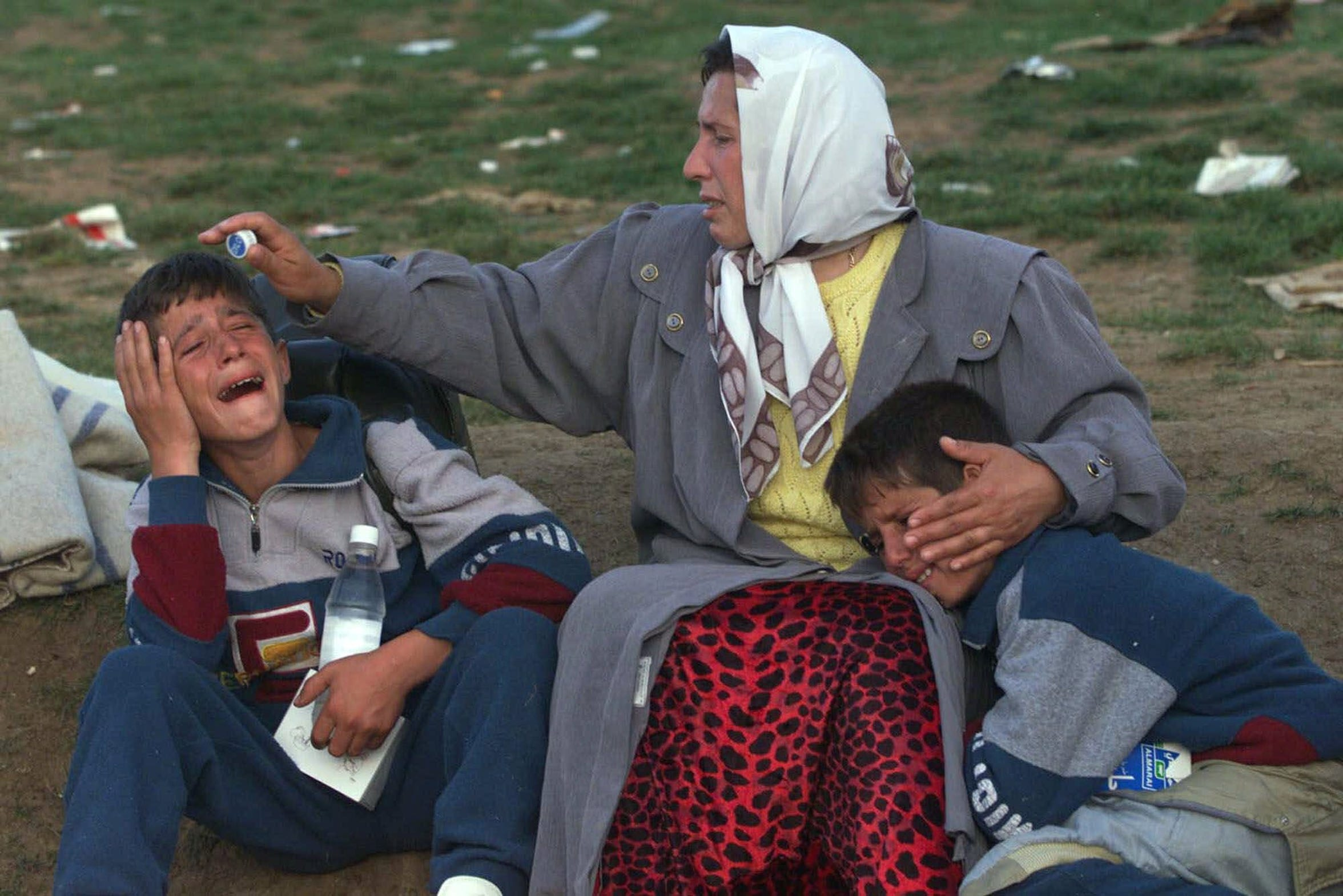 An ethnic Albanian woman consoles her twin sons