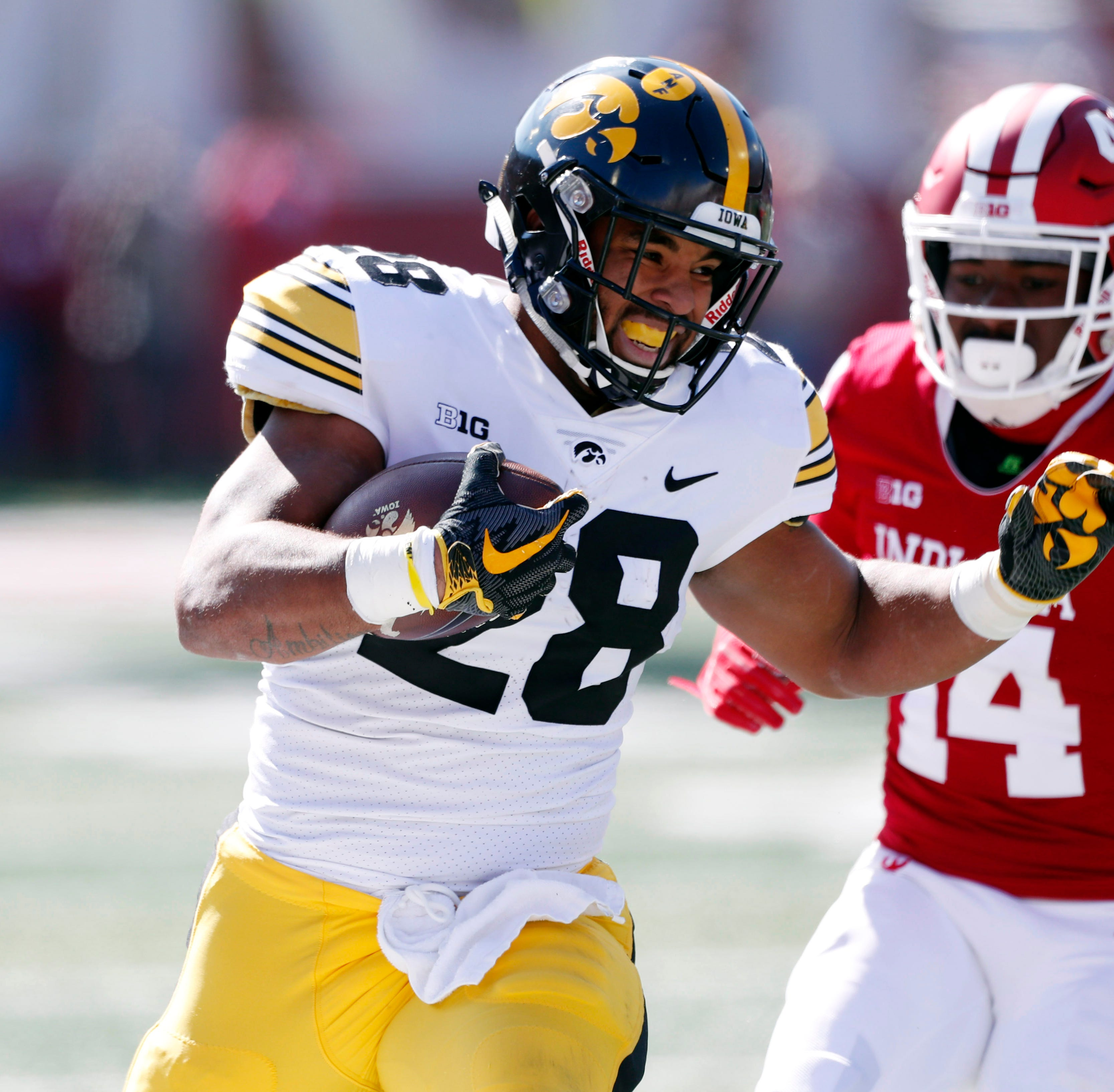 Hawkeyes running back Toren Young (28) runs with the ball against Indiana Hoosiers defensive back Andre Brown Jr. (14) during the first quarter at Memorial Stadium .