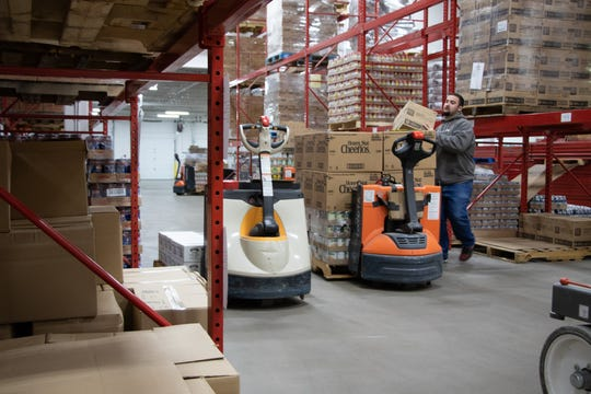 Chris Draman, a warehouse worker, moves inventory in the newly-upgraded Food Bank of Iowa. The renovations tripled the food bank's capacity.