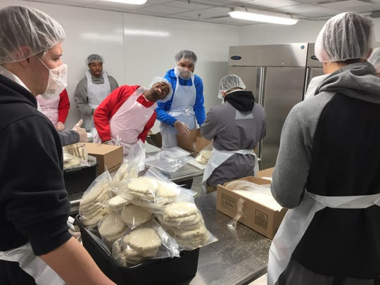 """Students from Central College break down packaged pork fritters into family-sized packages in the Food Bank of Iowa's newly added """"Clean Room."""""""