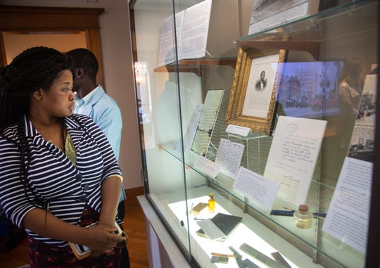 Rita Biah of Liberia looks over an exhibit on Alexander G. Clark at the Muscatine Art Center Tuesday, Oct. 9, 2018.