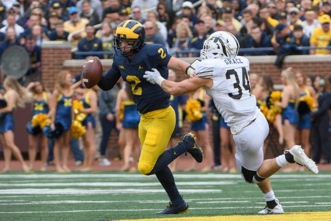 Michigan quarterback Shea Patterson pushes away Western Michigan linebacker Alex Grace while looking for an open man in the third quarter of their game last month.