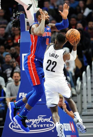 Pistons' Andre Drummond defends the Nets' Caris LeVert in the fourth quarter of Wednesday's regular-season opener.