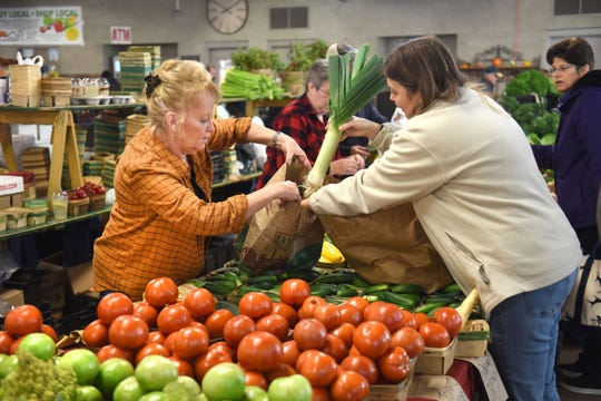 Diane Nykanen, right, of Van Houtte Farms in Armada, assists customers with their purchases on Oct.13 at the Royal Oak Farmers Market.