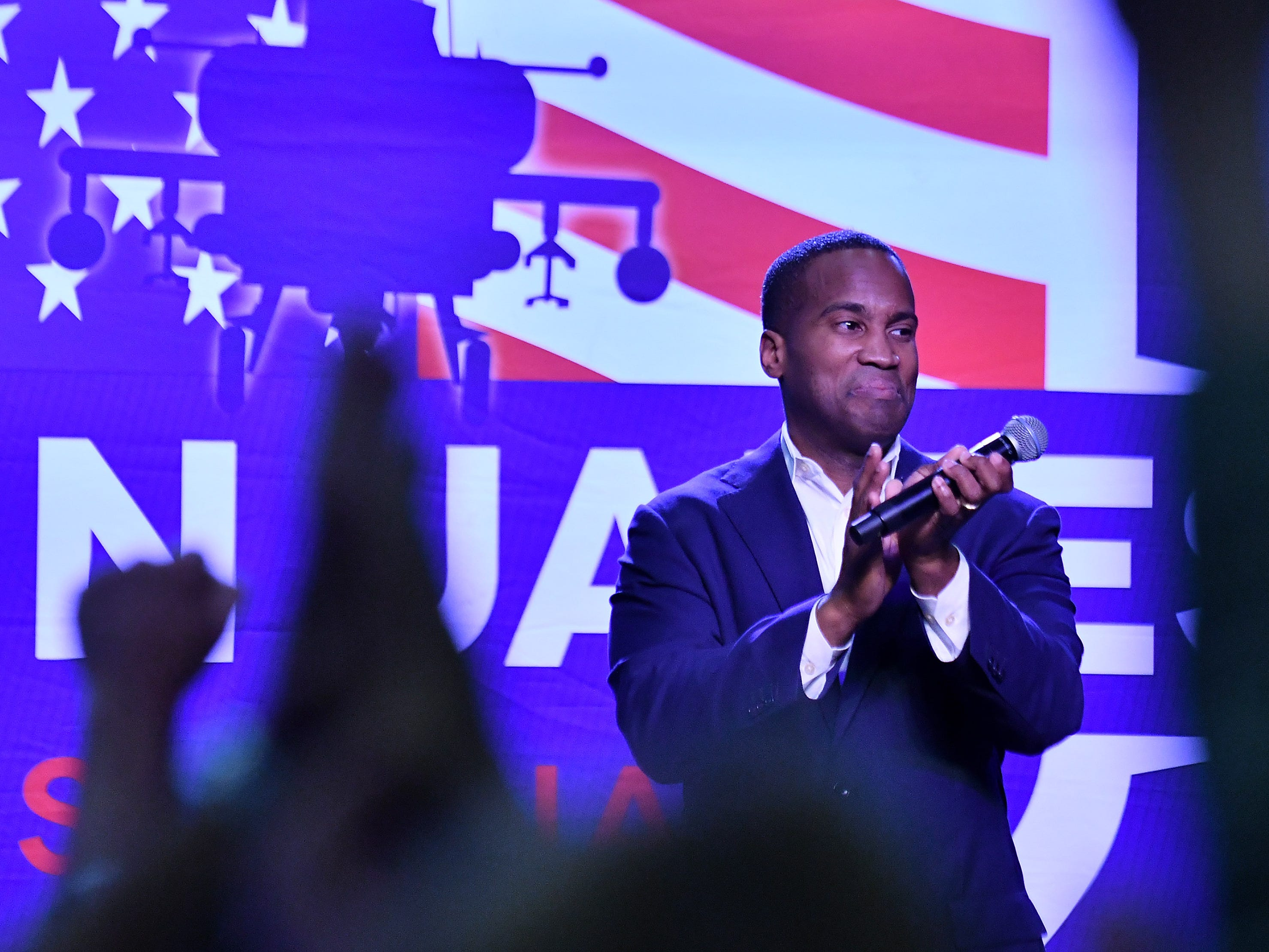 John James applauds his supporters during the rally.