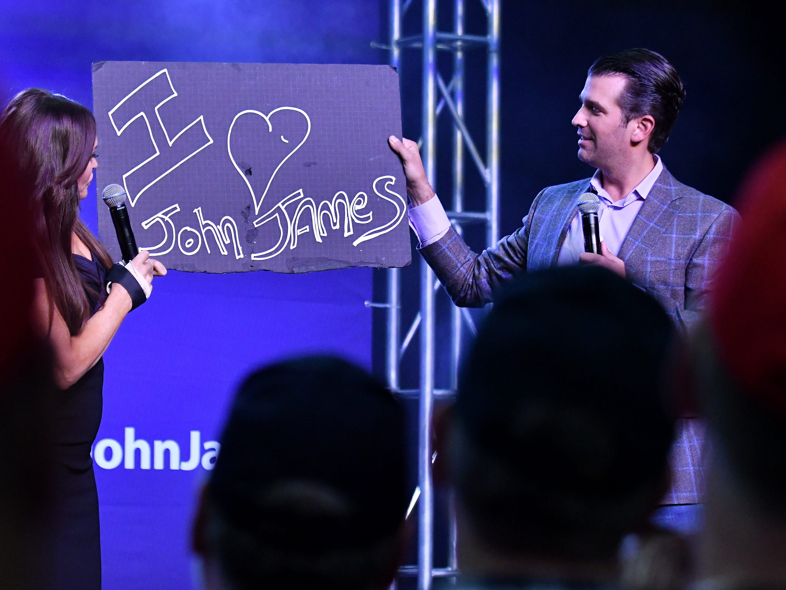 "Donald Trump, Jr. right, and Kimberly Guilfoyle hold up a ""I love John James"" sign during the rally."