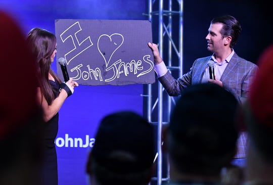 "Donald Trump Jr., right, and Kimberly Guilfoyle hold up an ""I love John James"" sign during a rally in 2018."