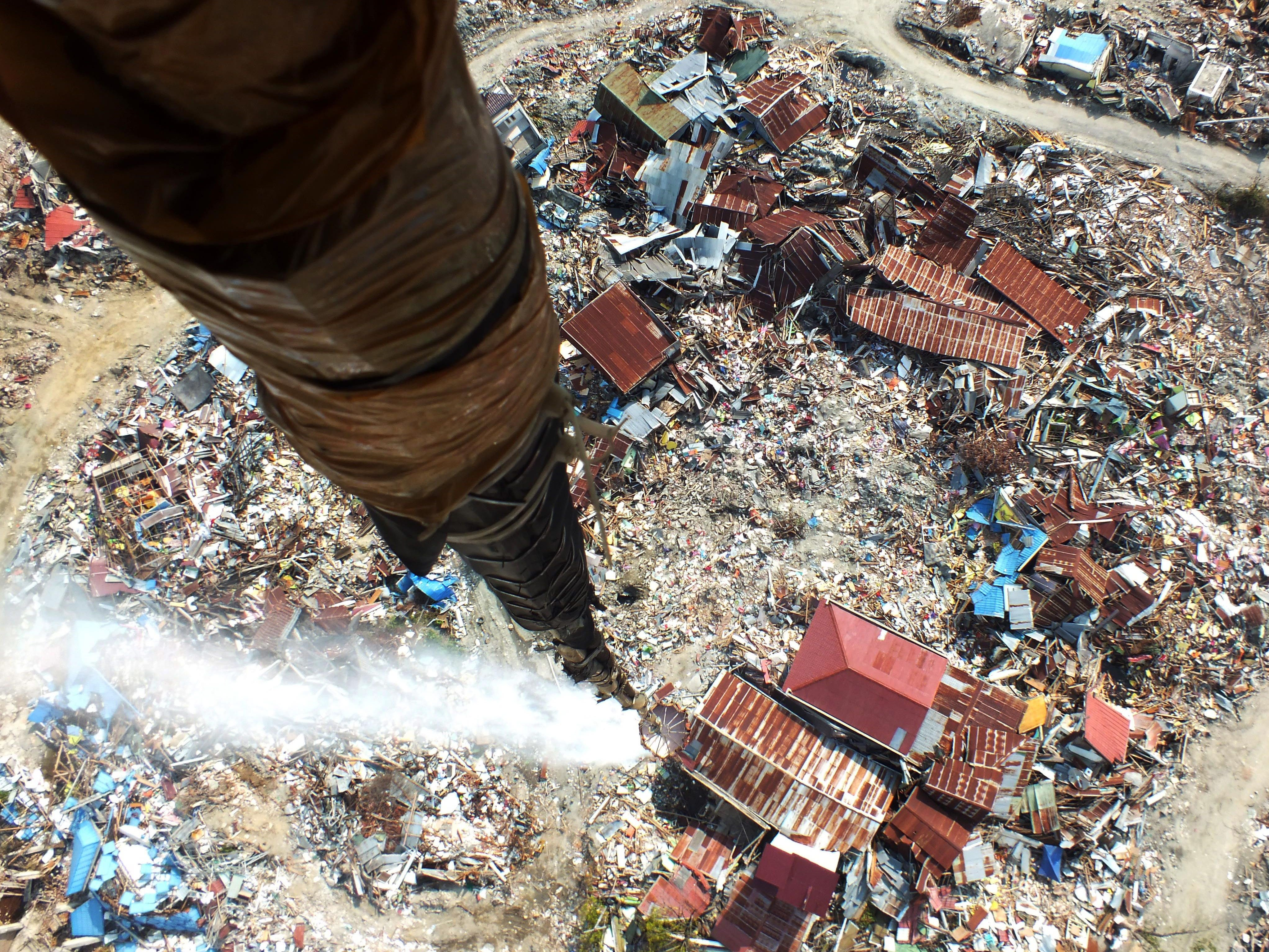 This picture taken from a helicopter on Oct. 18, 2018, shows disinfectant being released over an area affected by the Sept. 28 earthquake and where thousands are still feared buried, in an attempt to sterilize it in Palu. The World Bank on Oct. 14 announced funding of up to $1 billion for Indonesia after it was rocked by a string of recent disasters, including a deadly earthquake-tsunami that killed thousands.