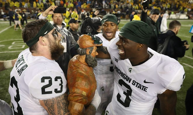 The Michigan State Spartans celebrate with the Paul Bunyan Trophy after defeating Michigan last season.