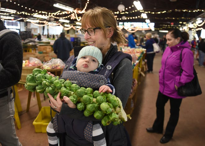 Kaitlyn Wojciak carries her infant Declan as she buys shops at the Royal Oak Farmers Market on Oct. 13.
