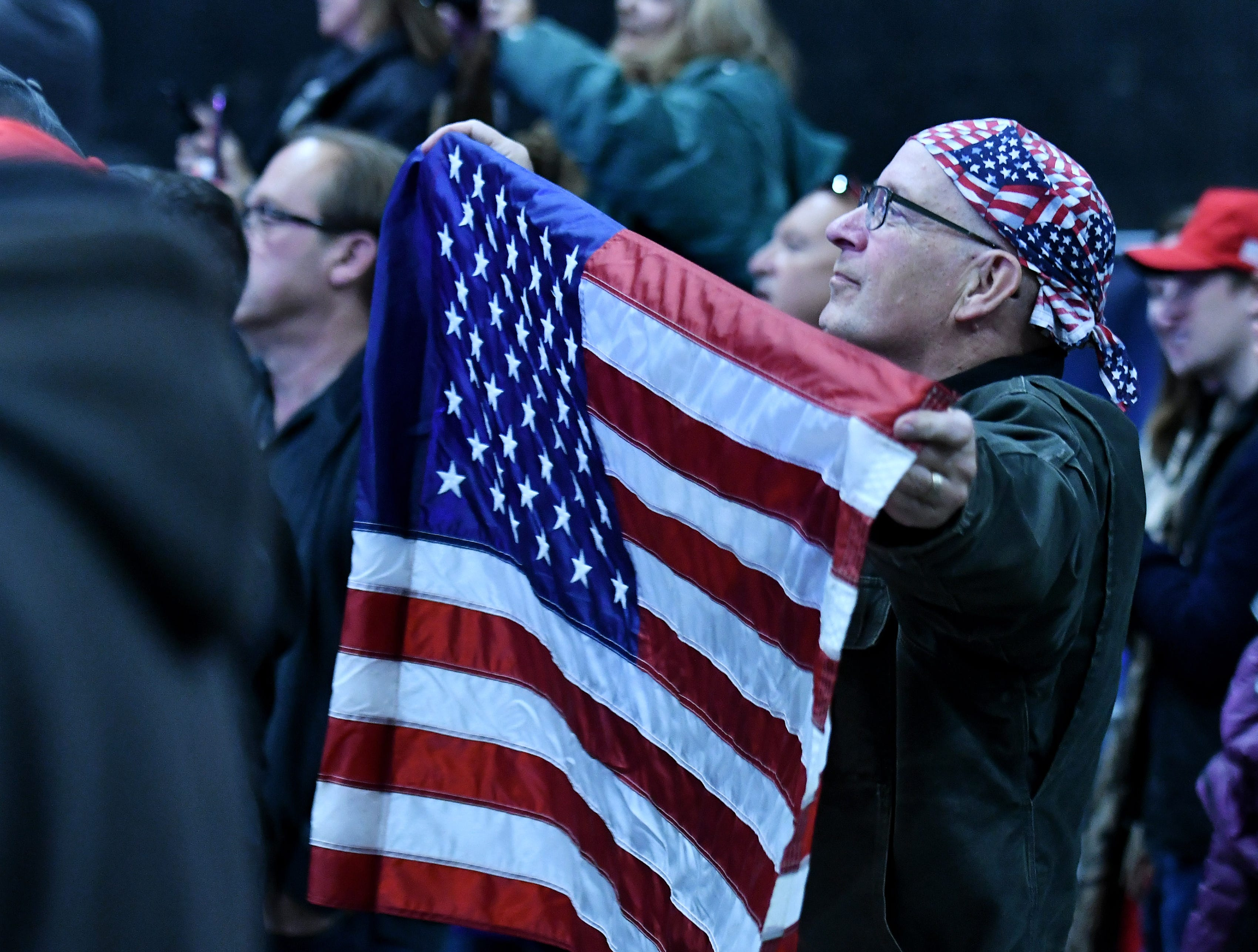 "Mark Jaruzel of Mayville, Mich. holds up a large flag during the rally.    ""Protect The American Dream Rally"" for Republican candidate for U.S. Senate John James at the Flagstar Strand Theatre in Pontiac, Mich. on Oct 17, 2018. 