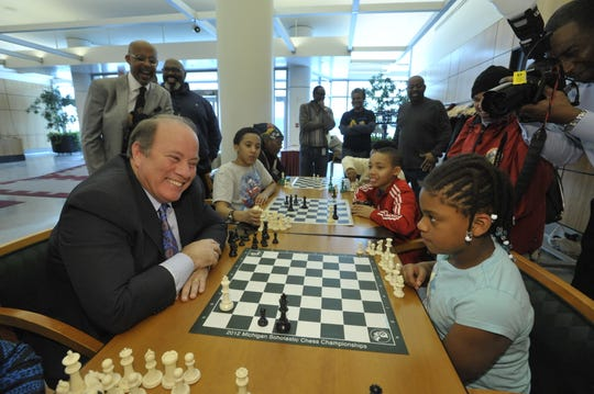 Detroit Mayor Mike Duggan plays Charisse Woods, a member of the Detroit City Chess Club, in 2014.
